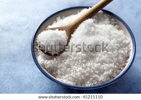 Bowl of sea salt flakes with a wooden serving spoon, over blue background.  Good detail and contrast in the flakes.