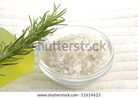 Bowl of sea salt with leaf and soap on towel