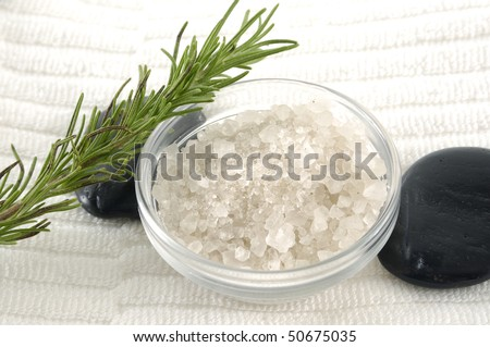 Bowl of sea salt with leaf and stone on towel