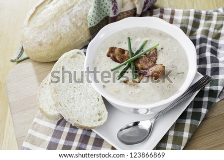 bowl of seafood soup set on a rustic table with a loaf of bread, very inviting - stock photo