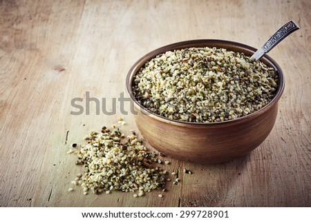 Bowl of shelled hemp seeds on wooden background - stock photo