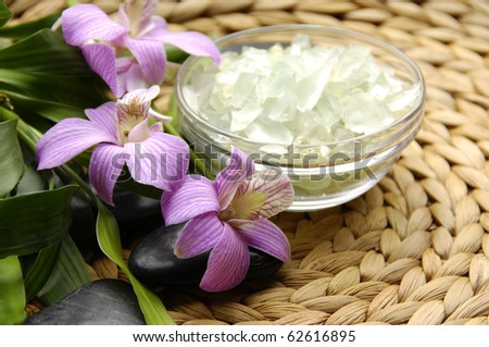 Bowl of slat and pink orchid with bamboo on woven mat background