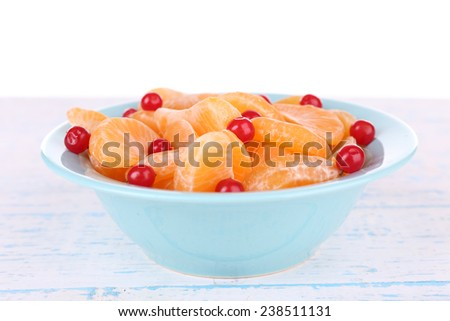 Bowl of slices mandarin with currants on color wooden surface isolated on white background