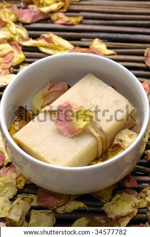 Bowl of soap with rose petals on bamboo mat - stock photo