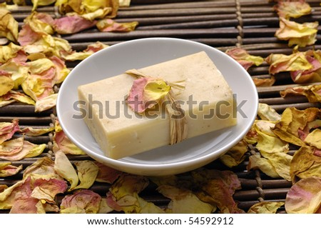 Bowl of soap with rose withered petals rose - stock photo