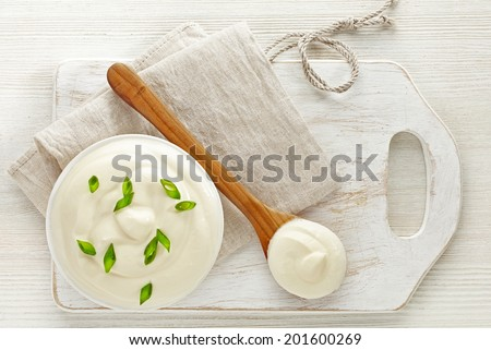 bowl of sour cream on white wooden cutting board, top view - stock photo