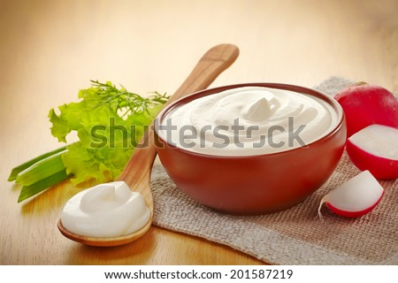 bowl of sour cream on wooden table - stock photo