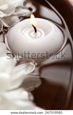 Bowl of spa water with flowers and candle, closeup - stock photo