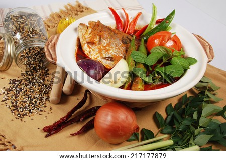 Bowl of spicy Asian curry fish head dish decorated with spices and ingredients on table mat. - stock photo