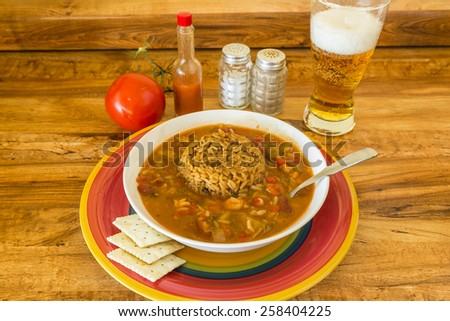Bowl of spicy Chicken Gumbo on colorful plate with frothy beer.  Sausage Dirty Rice in middle of gumbo. - stock photo
