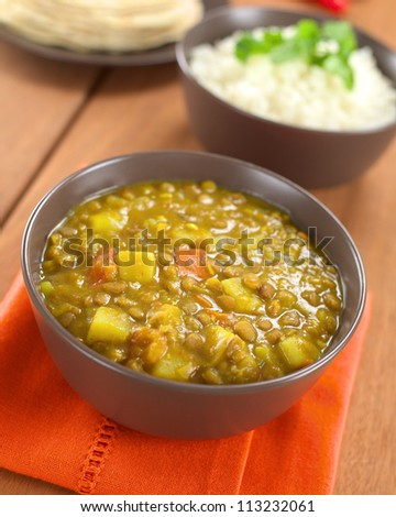 Bowl of spicy Indian dal (lentil) curry prepared with carrot and potato, rice and chapati flatbread in the back (Selective Focus, Focus one third into the curry) - stock photo