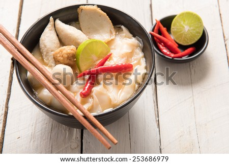 Bowl of spicy soup with noodles and vegetables for a delicious appetizer served with chopsticks and surrounded by fresh ingredients. - stock photo