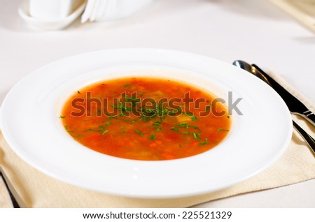 Bowl of spicy vegetable minestrone soup with fresh herb seasoning served in a wide brimmed dish at table - stock photo