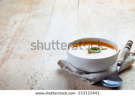 bowl of squash soup on a wooden table - stock photo