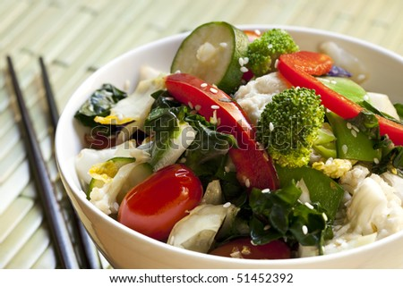 Bowl of stir-fried vegetables topped with sesame seeds.  With chopsticks.  Delicious healthy eating. - stock photo