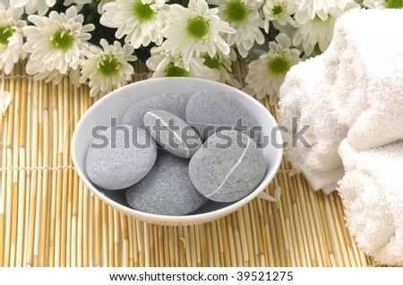 Bowl of stones with daisy and towel