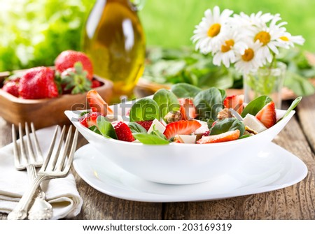 bowl of strawberry salad on wooden table - stock photo