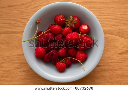 Bowl of summer fruit on a wooden table - stock photo
