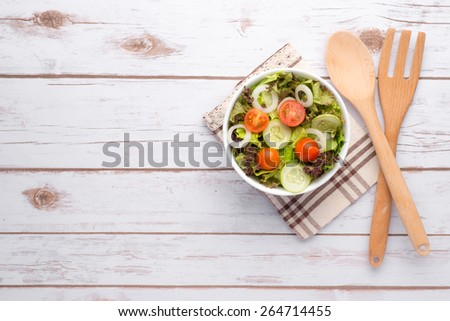 Bowl of Summer Salad. Fresh healthy salad on wooden table. View from above with copy space. bowl of leafy green salad with olives, tomatoes and cucumber. - stock photo