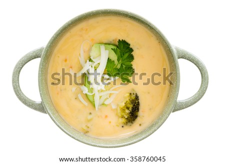 Bowl of tasty cream of broccoli soup garnished with fresh parsley and grated cheddar cheese, overhead view isolated on white - stock photo