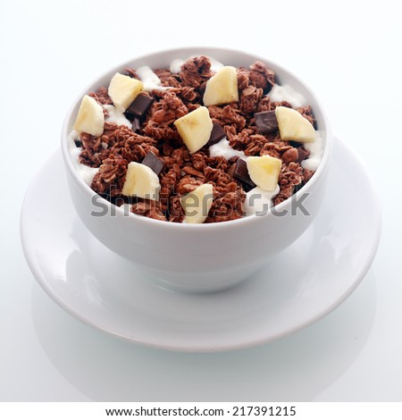 Bowl of tasty flavored chocolate breakfast cereal with diced fresh banana and chips of dark chocolate candy in a crunchy roasted muesli - stock photo