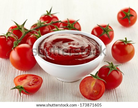 Bowl of tomato sauce and cherry tomatoes on white wooden background - stock photo