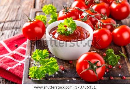 Bowl of tomato sauce and cherry tomatoes on wooden table, close-up. - stock photo