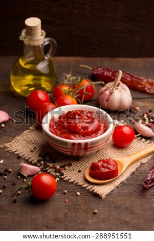Bowl of tomato sauce with fresh ingredients on dark  wooden background - stock photo