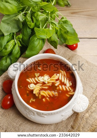 Bowl of tomato soup and basil plant in the background - stock photo