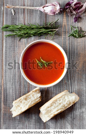 bowl of tomato soup on wooden background, top view - stock photo