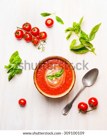 Bowl of tomato soup or gazpacho with spoon and basil on white wooden background, top view - stock photo