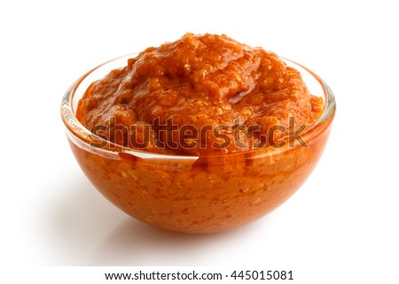 Bowl of traditional Italian red pesto isolated on white in perspective.