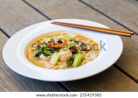 Bowl of traditional Thai tom yam soup with vegetables and prawns in a spicy aromatic broth served with chopsticks - stock photo