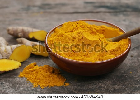 Bowl of Turmeric powder and turmeric roots on wooden background.