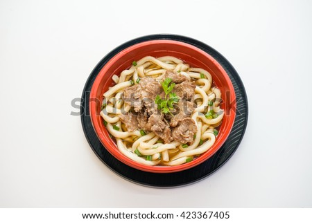 Bowl of udon noodles with beef isolated on white background