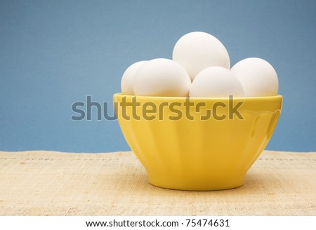 Bowl of uncooked white eggs in a yellow bowl. - stock photo