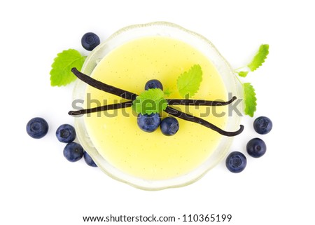 Bowl of vanilla pudding with vanilla beans and blueberries viewed from above on white - stock photo
