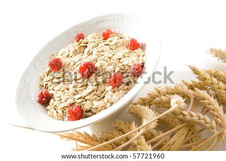 Bowl of wheat cereal with fresh raspberries. - stock photo