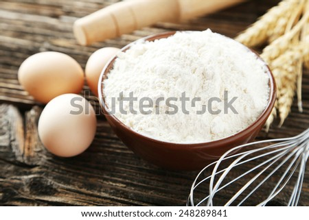 Bowl of wheat flour with eggs and whisk on brown wooden background - stock photo