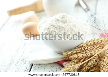 Bowl of wheat flour with eggs and whisk on white wooden background - stock photo