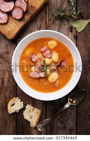 bowl of white bean soup on rustic wooden background - stock photo