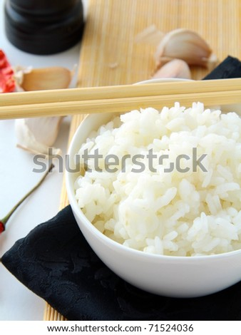 bowl of white fluffy rice with chopsticks and bamboo place mat - stock photo