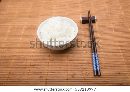 bowl of white rice on wood surface with chopsticks