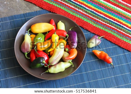 Bowl of whole, raw, colorful hot peppers on place mat in Peru