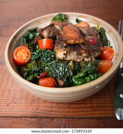 Bowl of Wilted Kale with Tomatoes, Cranberries, Broccoli and Pork on Top - stock photo