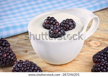 Bowl of yogurt and fresh Blackberries on a wooden table - stock photo