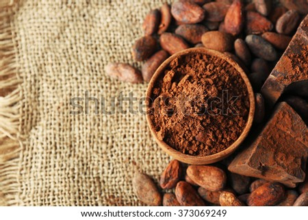 Bowl with aromatic cocoa powder and green leaf on a sacking, close up - stock photo
