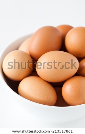 Bowl with brown eggs. Isolated on a white background. - stock photo