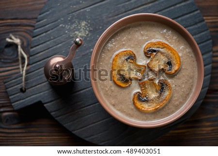 Bowl with champignon cream-soup on a serving board, top view