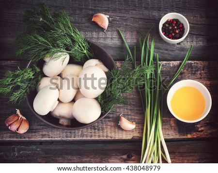 bowl with Champignon mushrooms, herbs and spices on an old background, tinted - stock photo
